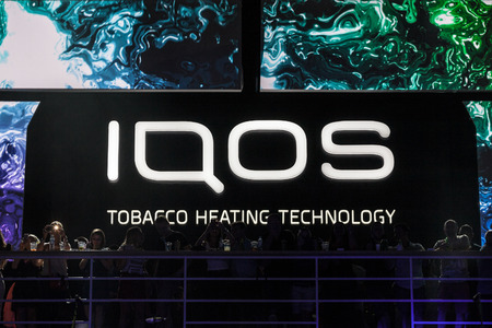 BELGRADE, SERBIA - AUGUST 16, 2018: Iqos logo in front of a bar terrace in Serbia. Iqos, beloning to Philip Morris International, is a tobacco heating cigarette system