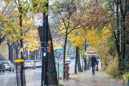 MONTREAL, CANADA - NOVEMBER 3, 2018: Man walking with an umbrella during a rainy autumn afternoon in a street of le Plateau, a residential distrct of Montreal, Quebec