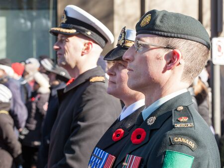 OTTAWA, CANADA - NOVEMBER 11, 2018: Soldiers from Canadian Army, two men, a woman, from Navy & ground forces, wearing remembrance poppy, standing on ceremony for Remembrance day Redakční