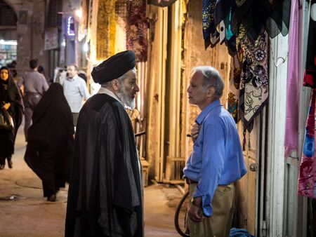 ISFAHAN, IRAN - AUGUST 20, 2016: Two men discussing in Isfahan bazar, one wearing black turban, meaning hes a Sayyid, pr Syed, a descendent of prophet Muhammad according to shia islam