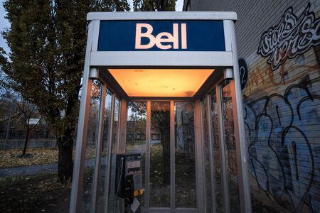 MONTREAL, CANADA - NOVEMBER 6, 2018: Bell Canada Payphone in Montreal in the evening. Bell Canada is one of the main phone booth providers and telephone carrier in the country