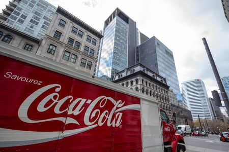 MONTREAL, CANADA - NOVEMBER 7, 2018: Coca Cola logo in on their delivery truck in the CBD of Montreal, Quebec, surrounded by business sckyscrapers.  Coca Cola is a soda brand of cola