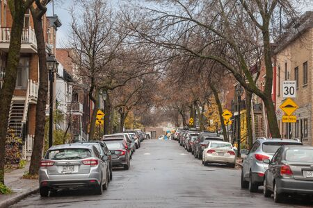 MONTREAL, CANADA - NOVEMBER 6, 2018: Typical north American residential street in autumn in Le Plateau, Montreal, Quebec, during an autumn afternoon, with cars parked
