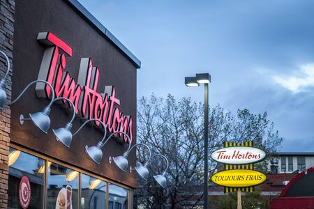 MONTREAL, CANADA - NOVEMBER 6, 2018: Tim Hortons logo in front of one of their restaurants in Quebec with their slogan in French in the background. Tim Hortons is a cafe and fastfood canadian brand  Picture of a sign with the logo of Tim Hortons on their  Editorial