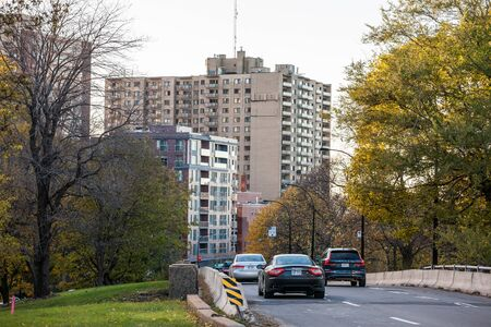 MONTREAL, CANADA - NOVEMBER 4, 2018: Car traffic on an urban road in Montreal, at fall, on the Cote des Neiges roads, with vehicles passing by, while Rochill appartments are visible in background