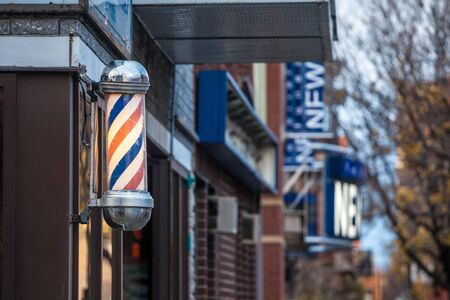 MONTREAL, CANADA - NOVEMBER 6, 2018: Typical American barbers pole seen in front of a barber shop of Montreal, Canada. This pole is a vintage sign indicating the presence of a male hairdresser salon.