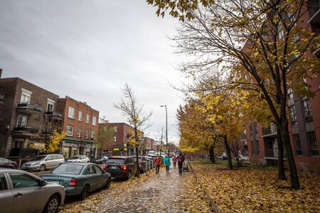 MONTREAL, CANADA - NOVEMBER 6, 2018: people walking with during a rainy autumn afternoon in a street of le Plateau, a residential distrct of Montreal, Quebec   Picture of a street of Le Plateau, in Montreal, with people walking under the rain during the a