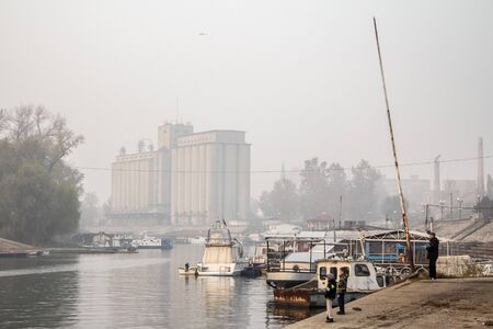 PANCEVO, SERBIA - NOVEMBER 2015: Children fishing on Tamis river, on Pancevo Waterfront, during a foggy afternoon. The iconic silos are visible in background.   Picture of Pancevo waterfront, in autumn, during a foggy afternoon. Pancevo is a city and the