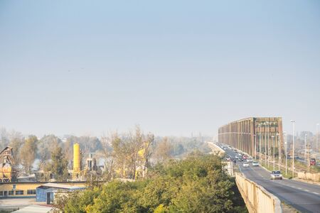 BELGRADE, SERBIA - AUGUST 2, 2015: Dense car traffic passing by the Pancevacki Most, or Pancevo bridge, during a day of bad atmospheric air quality with pollution cloud in the sky  picture of pancevacki most during a day of bad air quality, with a lot of