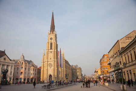 NOVI SAD, SERBIA - JANUARY 27, 2018: The Name of Mary Church, or Novi Sad catholic cathedral on a sunny afternoon with a crowd walking on Trg Slobode Square. This cathedral is the landmark of Novi Sad Editorial