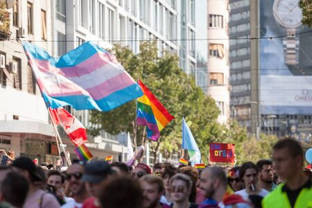 BELGRADE, SERBIA - SEPTEMBER 16, 2018:  Crowd raising and holding rainbow gay flags and transgender flags,during the Belgrade Gay Pride. The parade happened this year under huge police watch. Picture of a crowd of people holding and raising rainbow flag Editorial