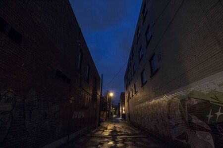 MONTREAL, CANADA - NOVEMBER 8, 2018: Dilapidated typical north American residential street in autumn in Montreal, Quebec, during a dark evening, with badly maintained brick buildings