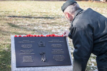 OTTAWA, CANADA - NOVEMBER 11, 2018: soldier putting remembrance poppy on the plaque to Nathan Cirillo, victim of the 2014 terrorist shootings, on National War memorial, on remembrance day Picture of a soldier placing a remembrance popyy on a plaque on P