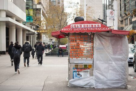 TORONTO, CANADA - NOVEMBER 13, 2018: Traditional North American hot dog stand in Downtown Toronto, Ontario, selling sausages, fries and drinks in a street near CBDPicture of a hot dog stand in the center of Toronto, Ontario, Canada, selling hot dogs, sa Editorial