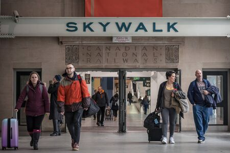 TORONTO, CANADA - NOVEMBER 13, 2018: Passengers passing by the Skywalk of of the train station of Union Station with the historic logo of Canadian National Railways, rebranded since as CNPicture of the old logo of the Canadian National Railways with pas Editorial