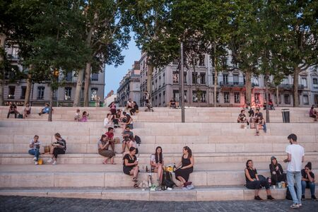 LYON, FRANCE - JULY 18, 2019: French people, mainly women and girls sitting on the riverbank of the Rhone (quais) in the evening while people are gathering for the tradition of apero