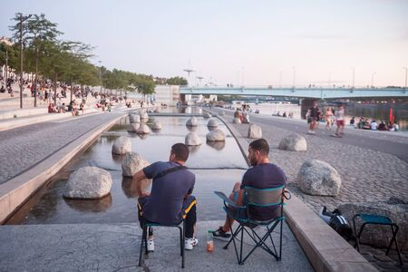 LYON, FRANCE - JULY 18, 2019: Two men sitting on the riverbank of the Rhone (quais) facing Pont de la Guillotiere bridge in the evening while people are gathering for the tradition of apero