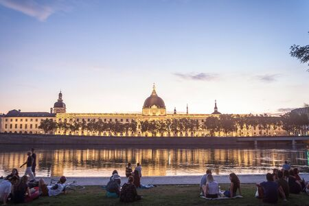 LYON, FRANCE - JULY 18, 2019:French people sitting on the riverbank of the Quais De Rhone, facing Hotel Dieu, one of the main monuments of the city for the tradition of apero