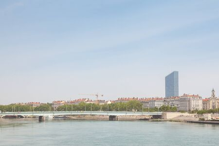 Pont de la Guillotiere bridge in Lyon, France over a panorama of the riverbank of the Rhone river (Quais de Rhone) with older buildings and a modern skyline in background Stock Photo