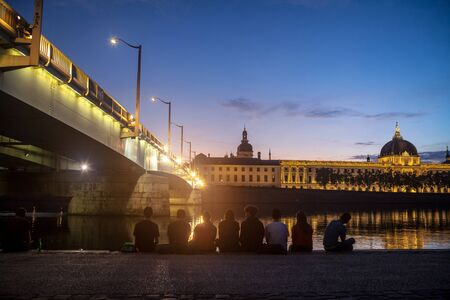 LYON, FRANCE - JULY 18, 2019: Young French people sitting on riverbank of Quais De Rhone, facing Hotel Dieu & Pont de la Guillotiere bridge, one of main monuments of the city for tradition of apero