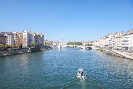 Boat approaching Pont Bonaparte bridge of Saone river near the Quais de Saone riverbank and riverside in the city center of Lyon during a summer afternoon