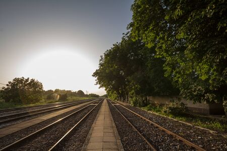 Railway tracks, rails and platforms in a rural train station in Alibunar, Serbia, taken during sunset with trees and a perspective  Picture of the train station of Alibunar, Serbia, taken during a warm summer dusk with railway tracks and platforms making a perspective effect