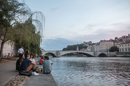 LYON, FRANCE - JULY 17, 2019: French people, mainly young men and women sitting on the riverbank of the Saone (quais) in the evening while people are gathering for the tradition of apero