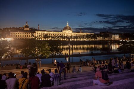 LYON, FRANCE - JULY 18, 2019: French people sitting on the riverbank of the Quais De Rhone, facing Hotel Dieu, one of the main monuments of the city for the tradition of apero