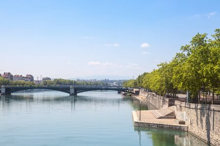 Pont de lUniversite bridge in Lyon, France over a panorama of the riverbank of the Rhone river (Quais de Rhone) with older buildings and the university bulding in background