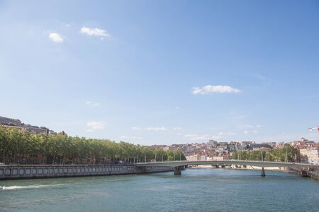 Panorama of Saone river and the Quais de Saone riverbank and riverside in the city center of Lyon, with a focus on the Pont Alphone Juin bridge, during a summer afternoon
