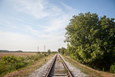 Abandoned railway track, on a defunct line in Serbia, Europe, rusty, surrounded by trees and a rural envirnoment, during a sunny afternoon  Picture of a perspective of a railroad track, taken on an abandoned line, during a sunny afternoon, in an agricultural environment in Serbia, Europe 版權商用圖片