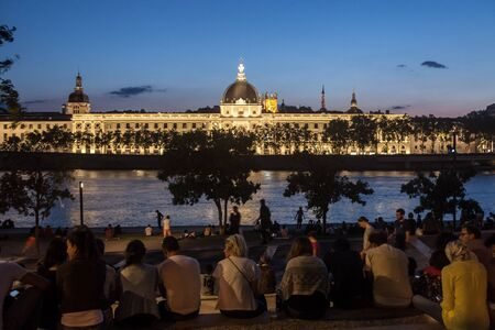 LYON, FRANCE - JULY 14, 2019: French people sitting on the riverbank of the Quais De Rhone, facing Hotel Dieu, one of the main monuments of the city for the tradition of apero