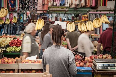 SUBOTICA, SERBIA - JULY 1, 2018: Young woman selling bananas and peaches on Subotica Buvljak Green market, while people are passing by ignoring her, with a speed blurPicture of a stall of Subotica Buvljak in Serbia, with an young girl standing while peo