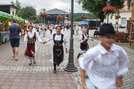 PANCEVO, SERBIA - JUNE 9, 2018: Serbian children wearing traditional folkloric costumes of Serbia with typical dresses for girls and peasant clothing for biys running in the streetsPicture of the main street of Pancevo with children running with their S Editorial