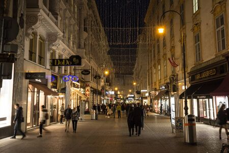 VIENNA, AUSTRIA - NOVEMBER 6, 2019: Kohlmarkt street, crowded, at night in winter with christmas decorations. Kohlmart is a pedestrian street with luxury stores in the city center of Vienna.Picture of Kohlmarkt street in Vienna, Austria, crowded with pe