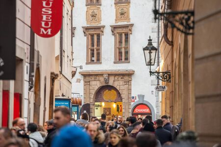 PRAGUE, CZECHIA - NOVEMBER 3, 2019: Crowd of tourists passing by and rushing in a narrow street being overpopulated in the medieval old town of Vienna, a major touristic destination.
