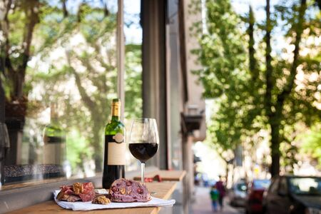 slices of baguette bread, brie cheese and saucisson (a cured meat from France) for appetizers with a Glass and bottle of French red wine, blurred in the background, on the table of a terrace of Paris.