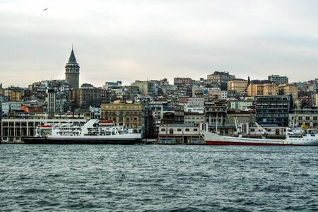 Galata Tower, on its hill, in Karakoy and Beyoglu district, taken during a cloudy winter afternoon, while the sea, ferry boats and cargo ships can be visible in foreground in Istanbul, Turkey.Picture of the Galata district, in Istanbul, Turkey, with its iconic Galata Tower. it is a quarter within the borough of Beyoglu, in Istanbul, known as Karakoy.