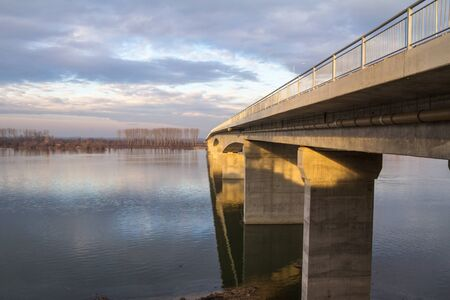 Reinforced concrete bridge used for road and car traffic passing by a large river, connecting two riverbanks of a countryside at dusk in winter, during a sunny afternoon.  Picture of a modern concrete bridge, made of grey cement, used for car traffic and roads, taken during a sunny afternoon, in winter, at dusk. Stock Photo