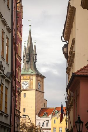 Typical narrow street of Stare Mesto, the historical center of Prague, Czech Republic, with a focus on the belfry and the clock tower of a medieval baroque church.Picture of a street of Prague, Czech Republic, taken in the historical center, called Stare mesto, or old town, centered on one of the medieval churches and its iconic belfry and clock tower. Reklamní fotografie