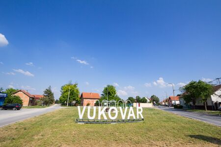 VUKOVAR, CROATIA, MAY 11, 2018: Vukovar sign at a road and street at the entrance of the city during a summer afternoon. It is a city on Slavonija, in Eastern Croatia.Picture of a monumental sign indicating the entrance to Vukovar, Croatia. Vukovar is a Stock Photo - 142586764