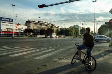 ZAGREB, CROATIA - JUNE 6, 2008: Cyclist waiting to cross Ulica Grada Vukovara street in Novi Zagreb, with heavy traffic. Novi Zagreb is the new part of the capital city of Croatia.Picture of a panorama of Ulica Grada Vukovara Street in Zagreb, Croatia,  Editorial