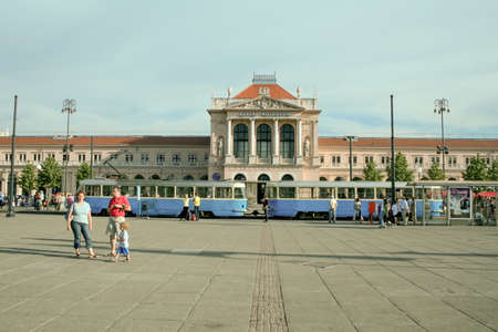 ZAGREB, CROATIA - JUNE 1, 2008: Zagreb Glavni Kolodvor, the Central train station of the city, with a tram in front. It is the main railway hub of the Croatian capital city.picture of the main facade of the Zagreb Glavni Kolodvor with pedestrians passin