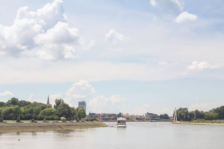 Panorama and skyline of Osijek from Drava river with skyscrapers & the Cathedral of the city. Osijek is a major city of the region of Slavonia in Northern Croatia.picture of the landscape of the city of Osijek, in Croatia, during a sunny afternoon, seen from the Drava river. Osijek is the fourth largest city in Croatia. It is the largest city and the economic and cultural centre of the eastern Croatian region of Slavonia