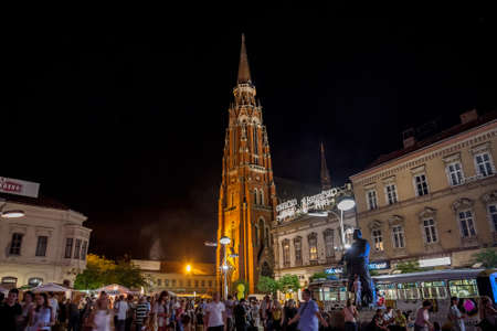 OSIJEK, CROATIA - AUGUST 25, 2017: Crowd gathering at a food market on the main square of Osijek, Ante Starcevic square. The Cathedral of the city can be seen in the background.