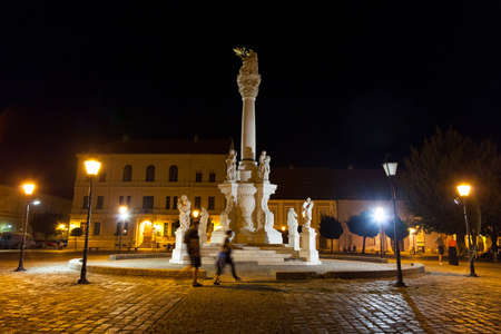 OSIJEK, CROATIA - AUGUST 25, 2017: Holy Trinity Column on the Trg Svetog Trojstva Square in the Osijek Fortress, called Tvrdja, by night, with people passing by. It is a major landmark of the city.