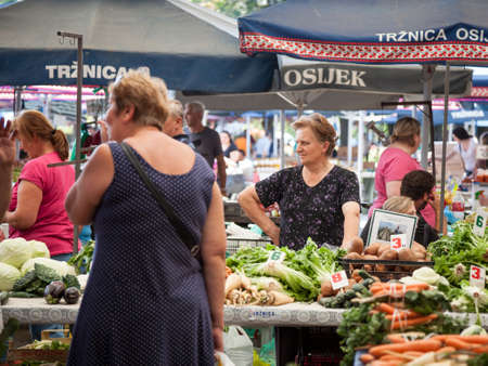 OSIJEK, CROATIA - AUGUST 26, 2017: Traditional scene of the Osijek green market with old women selling fruits and vegetables. Osijek is the center of Slavonija, the most agricultural zone of Croatia.Picture of Osijek Green market. Osijek is the capital