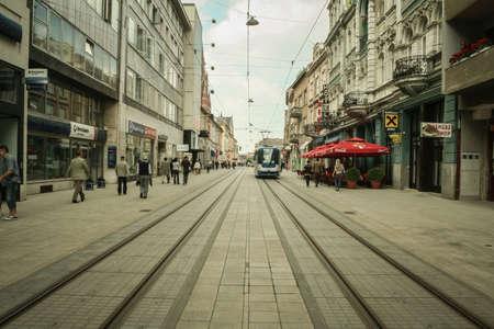 OSIJEK, CROATIA - JUNE 1, 2009: Main street of Osijek, Ulica Strossmayera Street, with pedestrian & tramway rails & a tram passing by. Osijek is the main city of Northern Croatian region of Slavonia.Picture of Strossmayer Street, the main street of Osij Editorial