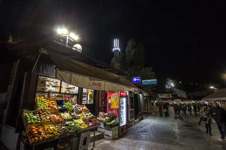 SARAJEVO, BOSNIA - APRIL 16, 2017: Street of Bascarsija district at night, with focus on fruits & vegetables merchant and souvenir shops. Bascarsija is symbol of Sarajevo, with its oriental architecture.Picture of one of Bascarsija's streets during a da