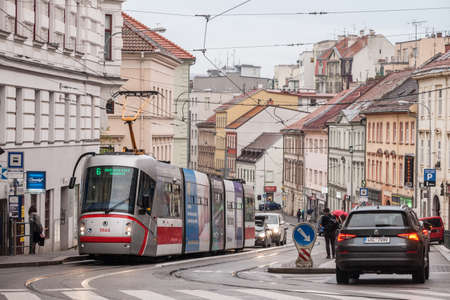 BRNO, CZECHIA - NOVEMBER 5, 2019: One tram, Skoda 13T, crossing cars driving in the city center of Brno. Also called Salina, these are the main transporation system of Brno, Moravia.Picture of a trams ready for departure in front of cars in Brno, Czech